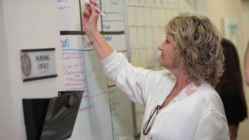 Doctor writing on board in nursing office
