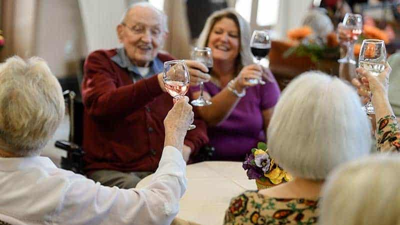 Senior group at table toasting glasses of wine