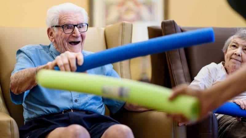 senior-man-smiling-holding-blue-noodle
