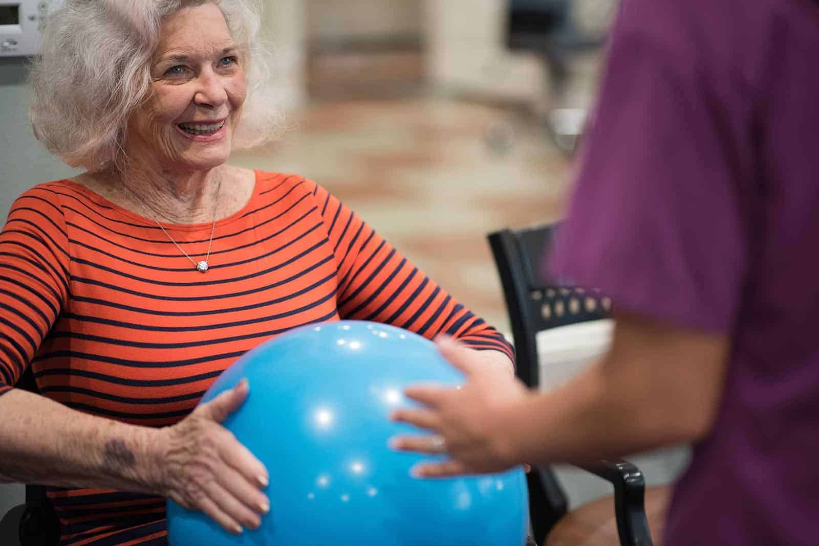 Senior woman holding rubber ball with nurse