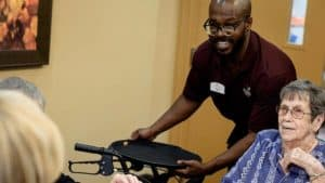 Staff bringing wheelchair to senior woman