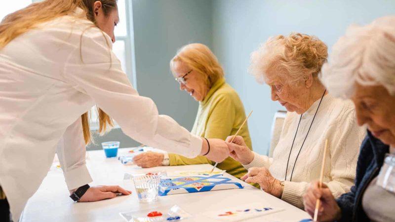 Staff helping three women paint