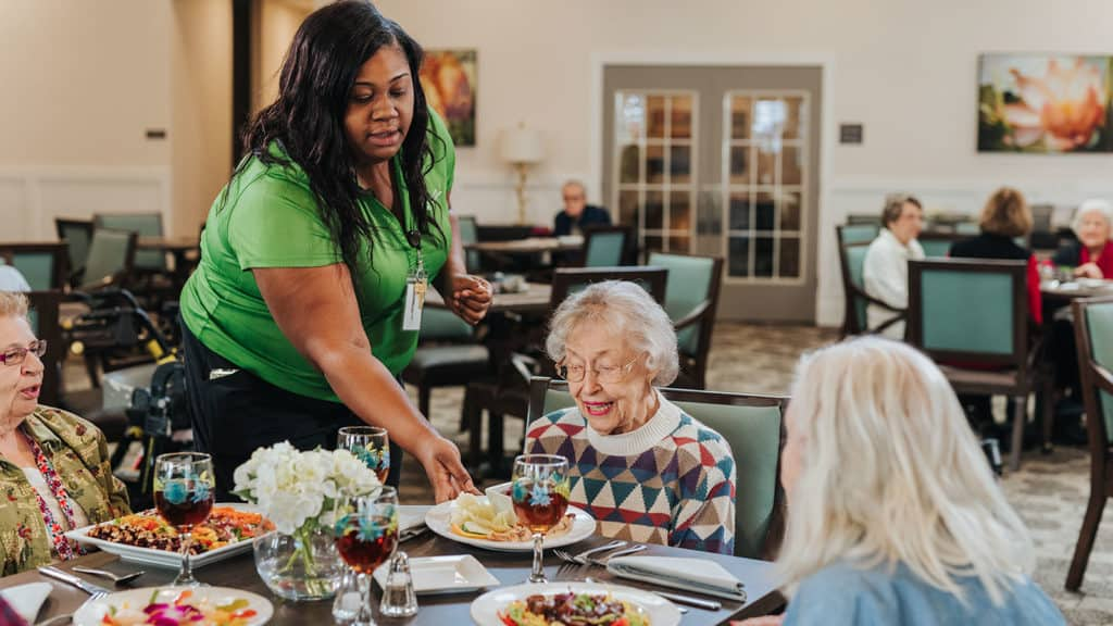 Staff member serving food to three seniors seated at table